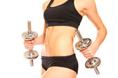 Belly of slim woman with two dumbbells on a white background — Stock Photo