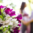 Stock Photo: Happy pregnant couple and bouquet of flowers in foreground