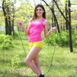 Smiling girl posing with skipping rope in summer park — Foto Stock #24858081