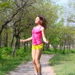 Young womjumping with skipping rope in summer park — Foto Stock #24858085