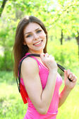 Smiling girl posing with a skipping rope on a hot summer day — Stock Photo