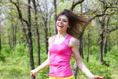 Happy girl with a skipping rope in a summer park — Stock Photo