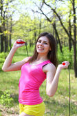 Smiling young woman with a skipping rope in a summer park — Stock Photo