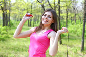 Beautiful young woman with a skipping rope in a summer park — Stock Photo