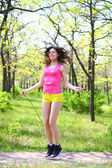 Happy young woman with skipping rope at summer park — Stock Photo
