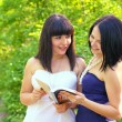 Two attractive brunette reading book in summer park — Photo #25320659