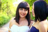 Zwei lächeln brünette frauen lesen eines buches in einem sommer-park — Stockfoto