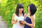 Two attractive brunette reading a book in a summer park — Stock Photo
