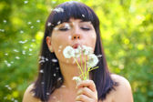 Attractive young woman blowing on a dandelion in the summer park — Stock Photo