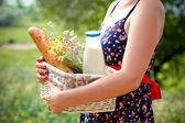 Woman holding a basket with bread, milk and flowers in a summer — Stock Photo