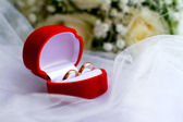 Wedding rings in a red box and a bouquet close-up — Stock Photo