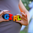 Pregnant woman holding the word girl — Stockfoto