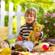 Little boy with an apple and a teddy bear showing tongue — Stock Photo #33438865