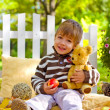 Little boy with an apple and a teddy bear sitting in the autumn — Stock Photo #33438885