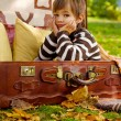 Sad little boy sitting in an old suitcase — Stock Photo