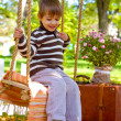 Little boy sitting on a swing in the autumn park — Stock Photo
