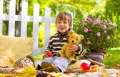 Little boy with an apple and a teddy bear showing tongue — Stock Photo