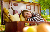 Little boy sleeps in a large suitcase in the autumn park — Stok fotoğraf