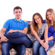 Foto Stock: Friends sitting on a couch and watching television on white back