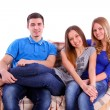 Friends sitting on a couch and watching television on white back — Stok fotoğraf