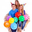 Three friends sitting on a couch with hats and balloons — Stock Photo #40295845