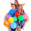Three friends sitting on a couch with hats and balloons — Stock Photo