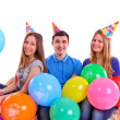 Three friends in hats with balloons sitting on the couch — Stock Photo