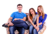 Friends sitting on a couch and watching television on white back — Stock Photo