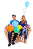 Friends sitting on a sofa with balloons isolated — Stock Photo