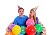 Friends sitting on a sofa with balloons and hats — Stock Photo