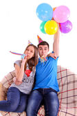 Couple with hats and balloons sitting on the couch — Stock Photo