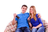 Young people sitting on a sofa and drinking Coca Cola isolated — ストック写真