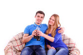 Young people sitting on a sofa and drinking Coca Cola — Stockfoto