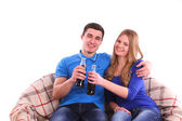 Young couple sitting on a sofa and drinking Coca Cola — Stockfoto