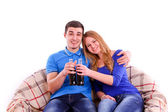 Young couple sitting on a sofa and drinking Coca Cola isolated — ストック写真