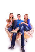 Happy friends sitting on a sofa and drinking Coca Cola — Stockfoto