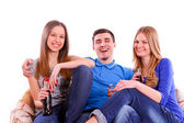 Happy friends sitting on a sofa and drinking Coca Cola isolated — ストック写真