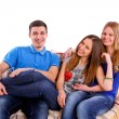 Three happy friends sitting on a couch isolated — Stock Photo