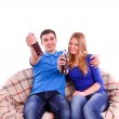 Young couple sitting on a couch and drinking a soda — Stock Photo