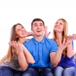 Guy and two girls sitting on the couch and looking up — Stock Photo #40551297