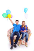 Young couple sitting on a sofa with balloons — Stock Photo