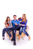 Three friends sitting on a couch and drinking a soda — ストック写真