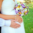 Hands with rings and bouquet — Stock Photo