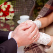 Couple holding hands at wooden table — Stock Photo