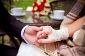 Couple holding hands at wooden table — Stok fotoğraf