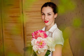 Beautiful young woman with a bouquet of peonies indoors — Stock Photo