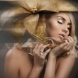 Portrait of woman with golden flower — Stock Photo #13393684