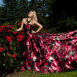 Beautiful fashionable woman in a garden with roses - Stock Photo