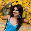 Stock Photo: Woman with yellow leaves in autumn