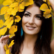 Woman with yellow leaves in autumn — Stock Photo #16822597